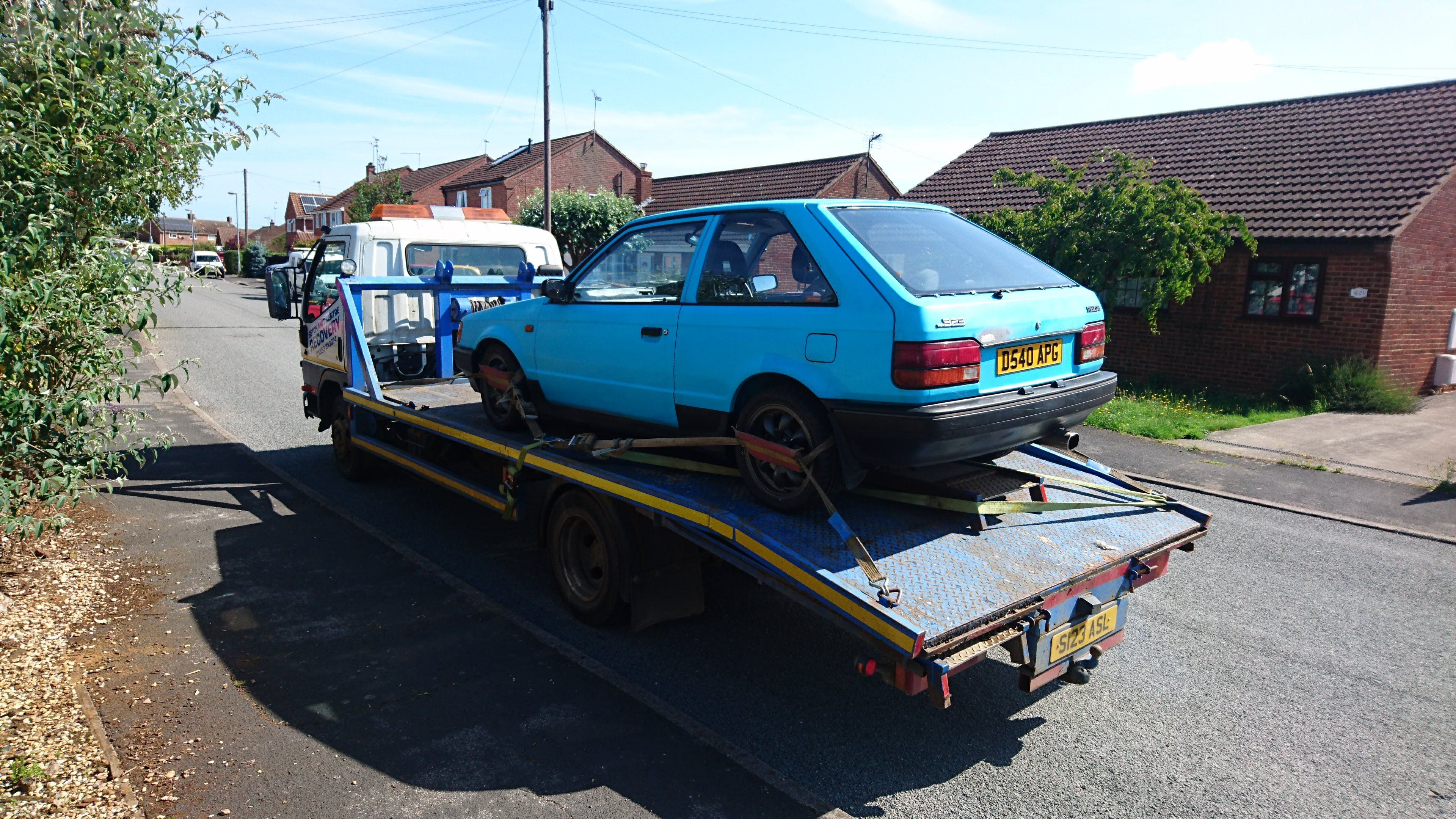Mazda 323 GTX loaded onto a recovery truck