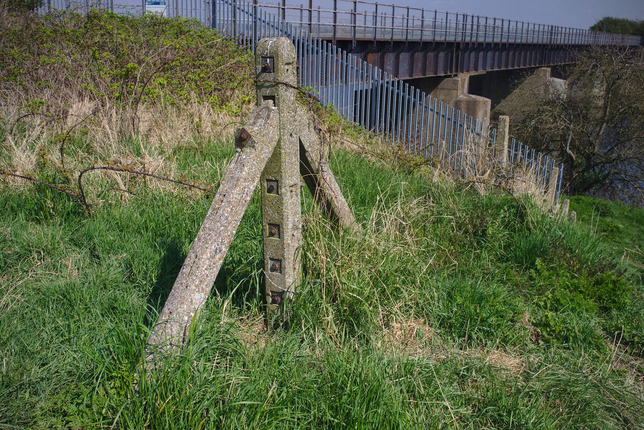 An old railway fence post, with the Magdalen railway bridge just about visible in the background.