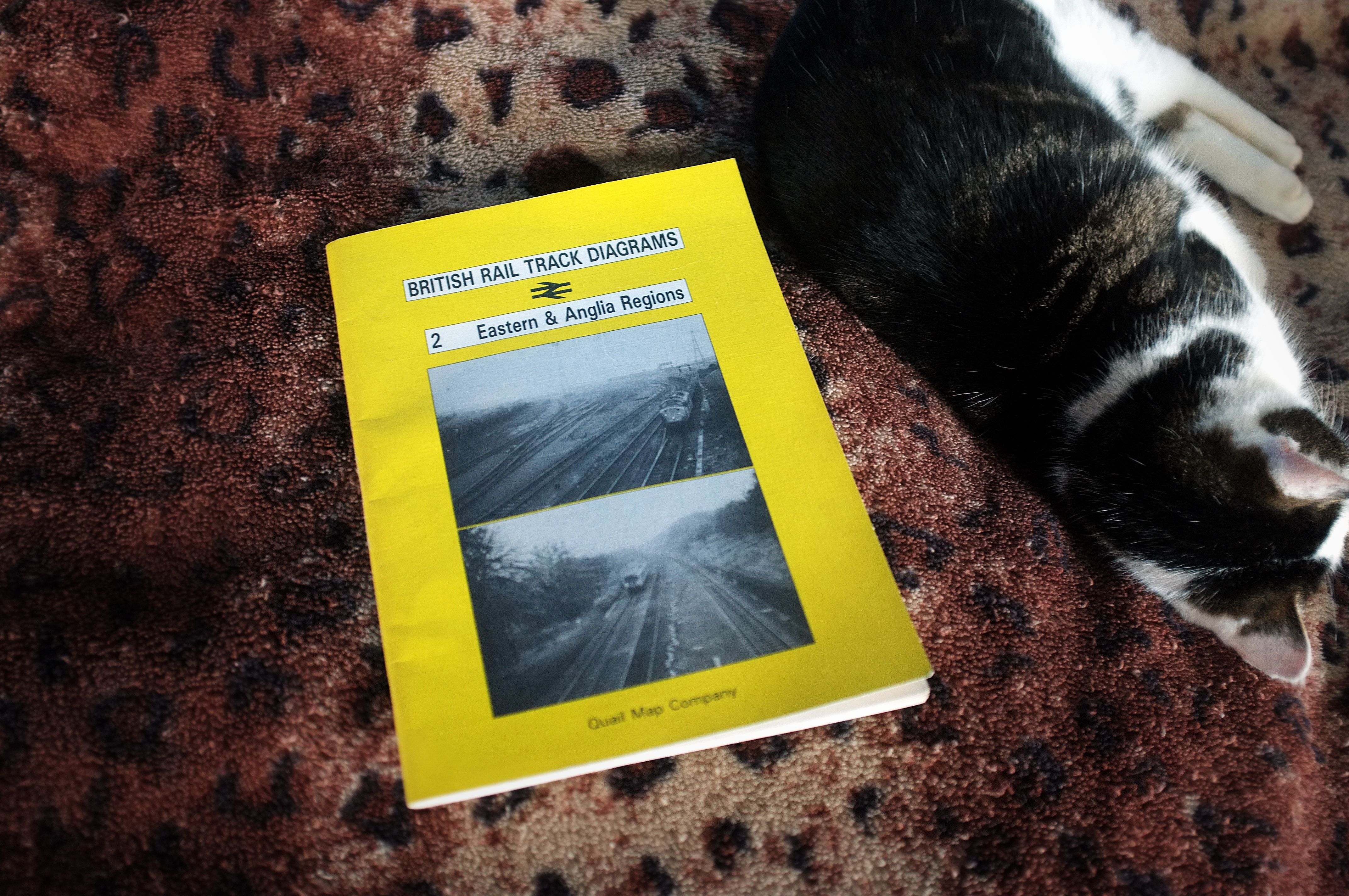 """My cat, asleep next to a copy of """"British Rail Track Diagrams"""" No 2, Eastern Region"""